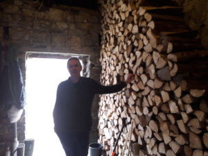 Brian stands beside the remainder of the logs from last summer's delivery, for his log boiler for home heating.