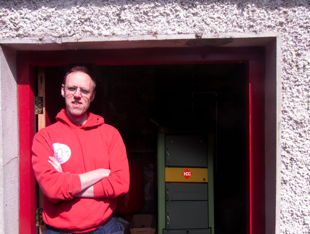David Walsh-Kemmis stands by the door of the boiler shed at Ballykilcavan House that houses the HDG-R boiler and the 2000L accumulator tank.